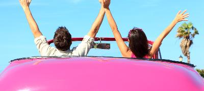 Jeune couple heureux dans leur voiture rose